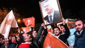 Supporters of Turkey's Justice and Development Party (AKP) hold up a portrait of Turkish President Recep Tayyip Erdogan as they celebrate in Istanbul after the first results in the country's general election on November 1, 2015. (AFP/Ozan Kose)
