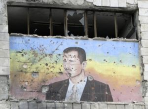 A picture of Bashar al-Assad riddled with holes on the facade of the police academy in Aleppo, after it was captured by Free Syrian Army fighters, March 4, 2013. (REUTERS/Mahmoud Hassano)