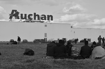 Black and white image of a group of migrants sitting in a circle in a grassy field, with their backs to the lens. A supermarket building resides in the background, with the name 'Auchan' written in large letters on the roof. Photo by Dreptul la Oraș