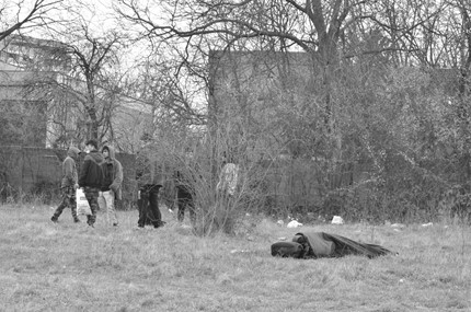 Black and white image of a grassy field with leafless trees in the background. On the left side there is a group of four migrants standing in a circle, while on the right side there is one person sleeping in a sleeping bag on the ground. Photo by Dreptul la Oraș