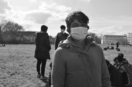 Black and white image of a young Afghan boy, wearing a winter coat and facemask. Around him, in the back, there are several other people sitting on the grassy field or standing up. Several buildings are visible in the distance. Photo by Dreptul la Oraș